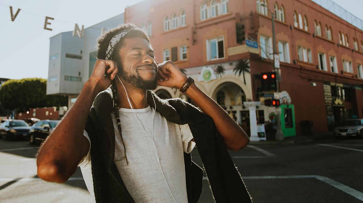 man wearing earphones on a sidewalk