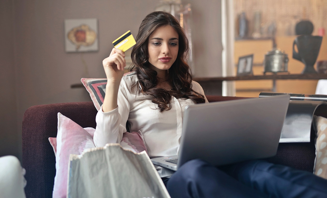Person facing laptop computer while holding a credit card