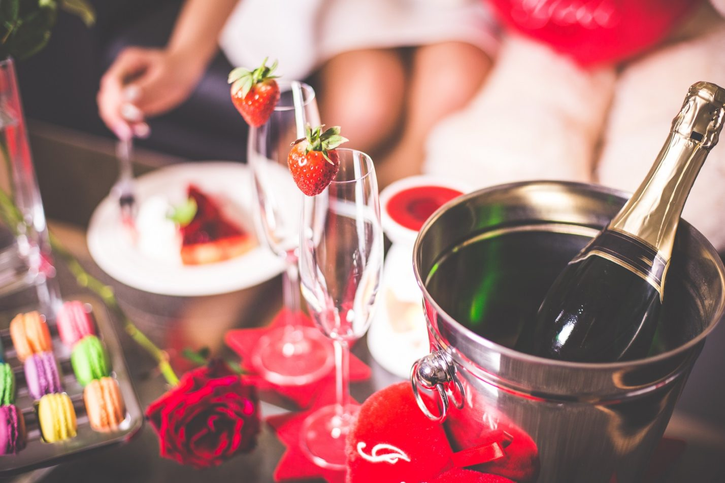 Two champagne flutes with strawberries on the rim, next to a bottle of champagne